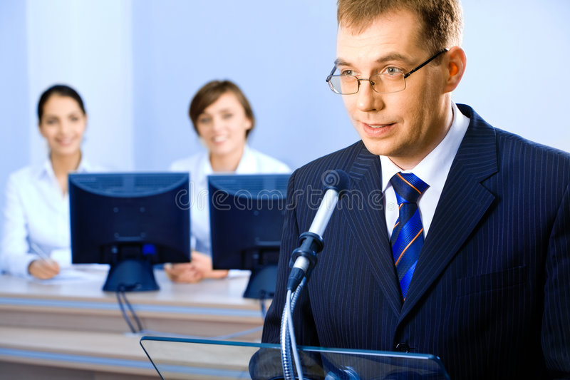 Business speech. Successful business man delivers oneself of a speech at a conference stock photography