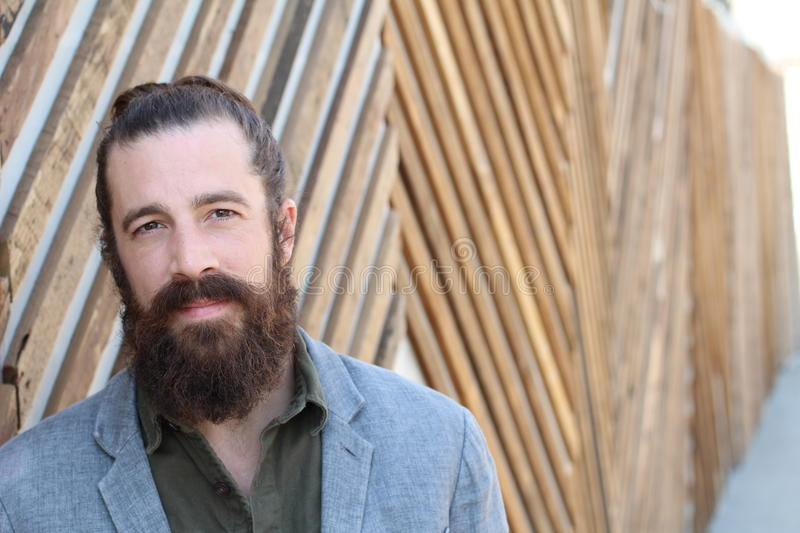 Business, startup, inspiration and people concept - happy Mediterranean man with beard and hair bun. Copy space on the right stock image