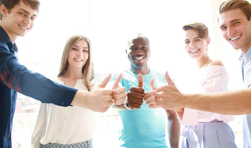 Business, startup and office concept - happy creative team showing thumbs up in office. royalty free stock images