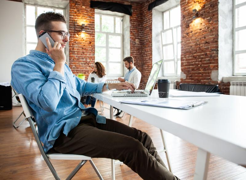 Business, startup and people concept - happy businessman or creative male office worker with computer calling on. Smarphone stock image