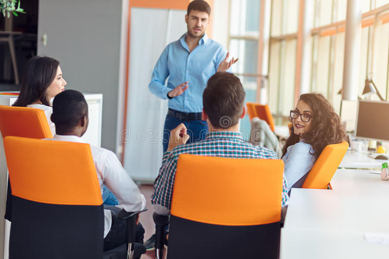 Business, startup, presentation, strategy and people concept - man making presentation to creative team at office. Business, startup, presentation, strategy and royalty free stock photography