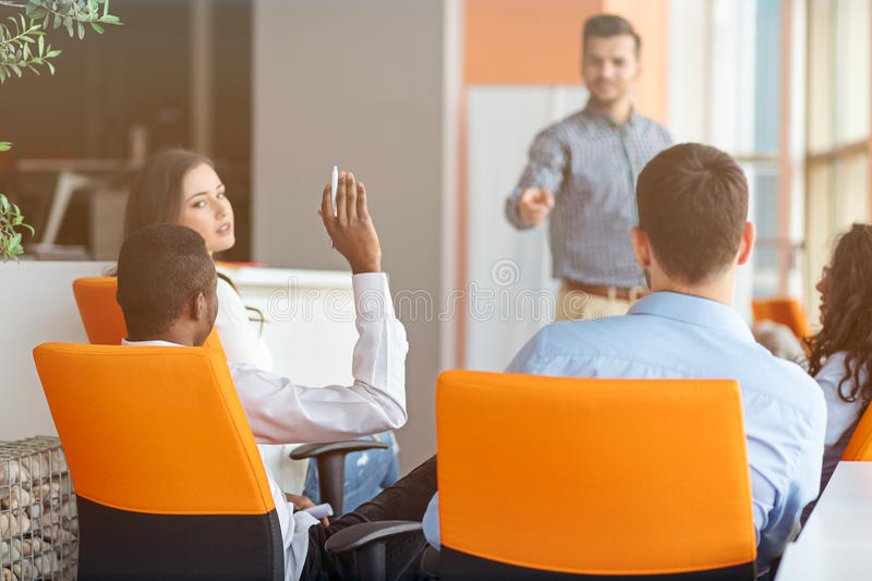 Business, startup, presentation, strategy and people concept - man on presentation with group of people at office. Business, startup, presentation, strategy and stock image