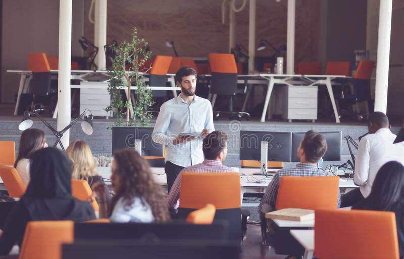 Business, startup, presentation, strategy and people concept - man on presentation with group of people at office. Business, startup, presentation, strategy and royalty free stock photo