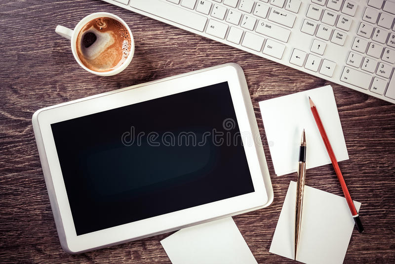 Business still life concept. White tablet pc and stationary on wooden table royalty free stock photo