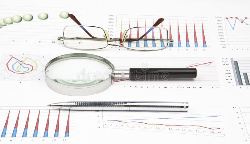 Business still-life. Of graph, eyeglasses, magnifier, shiny pen royalty free stock photo