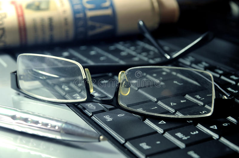 Business Still Life. Newspaper, glasses and ball pen on top of a laptop stock photo