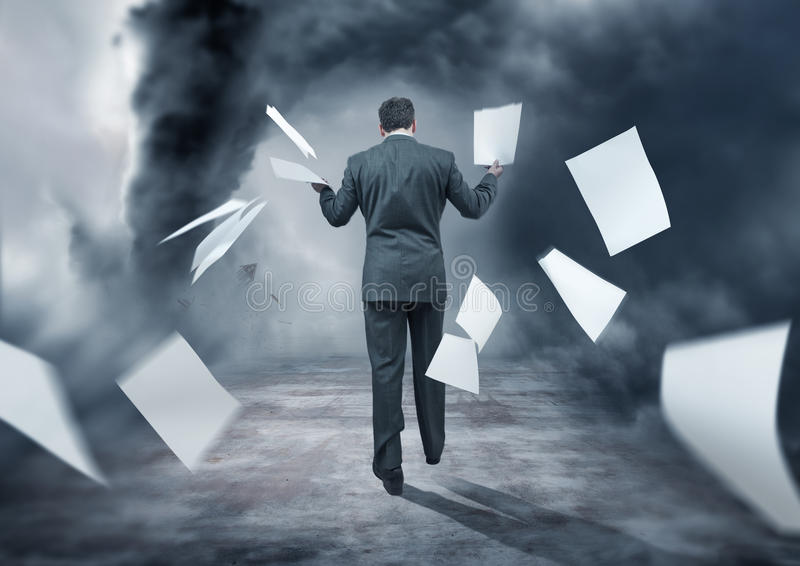 Business Storm. A Businessman Letting go of paperwork in a storm