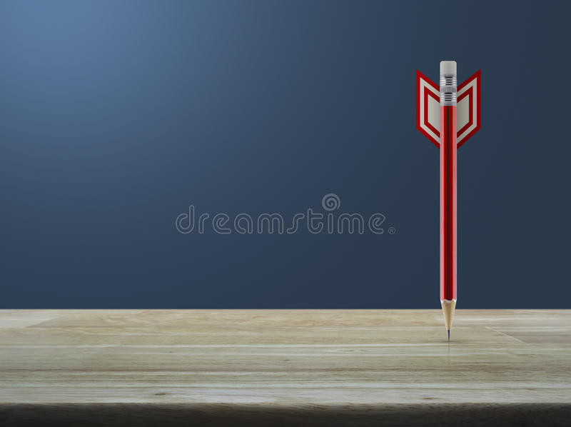 Business strategy concept. Red pencil in the shape of a dart on wooden table over light gradient blue background, Business strategy concept stock photography