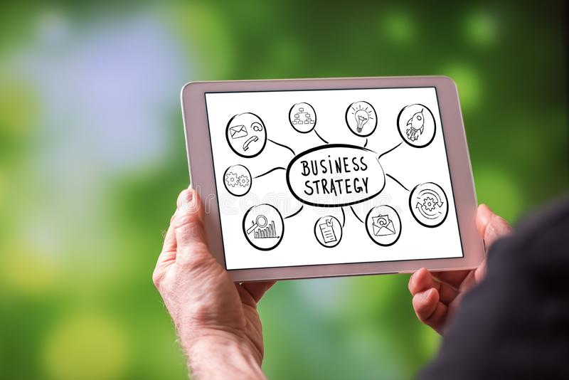 Business strategy concept on a tablet. Man holding a tablet showing business strategy concept stock photography