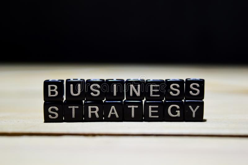 Business Strategy concept wooden blocks on the table. With personal development and motivation concept on blurred or black background royalty free stock image