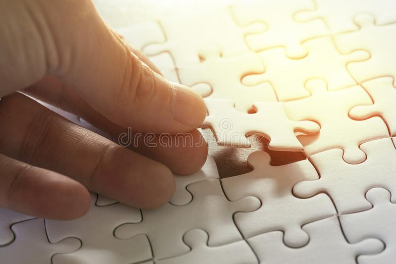 Business strategy, finish or finalize, problem solution metaphor. Concept, man holding last piece of jigsaw puzzle putting to complete the perfect game royalty free stock photos