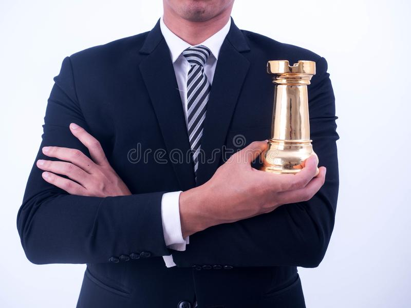 Business strategy and leadership concept - Businessman holds a chess symbol of the leader royalty free stock photography