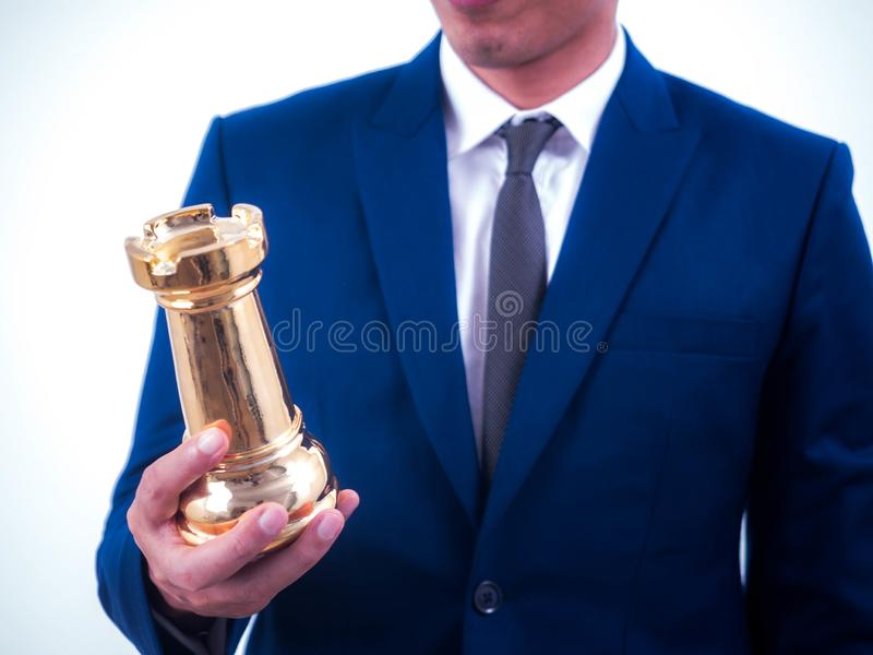 Business strategy and leadership concept - Businessman holds a chess symbol of the leader royalty free stock photo