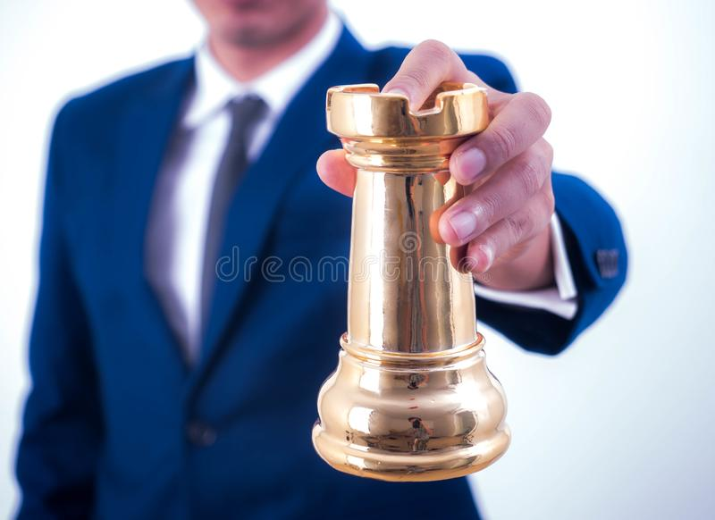 Business strategy and leadership concept - Businessman holds a chess symbol of the leader stock image