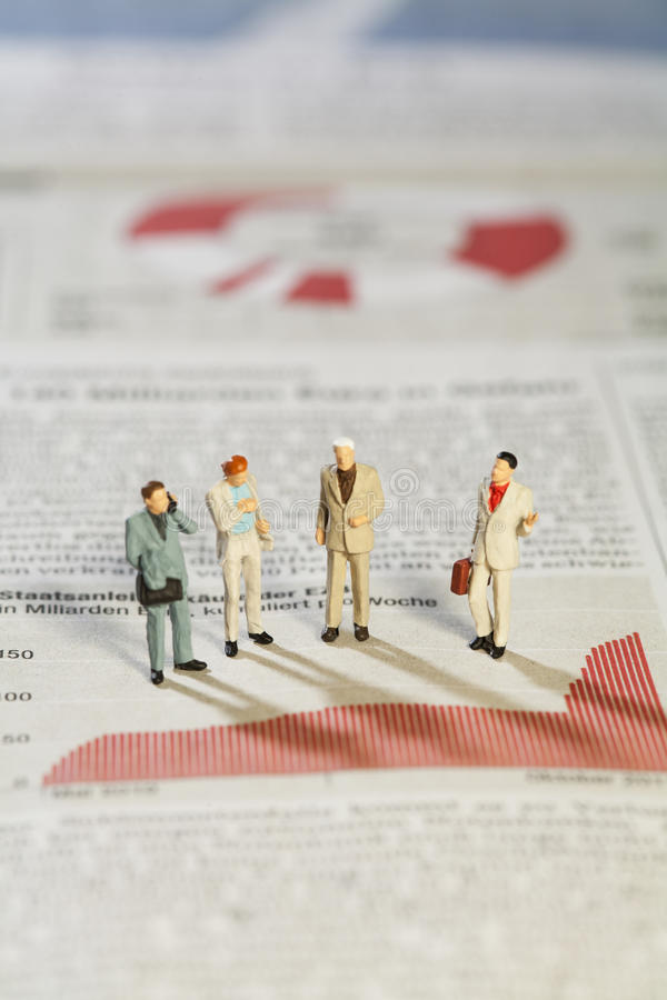 Business Strategy Meeting. Four miniature models of businessmen standing above a bar graph as though in a meeting royalty free stock images