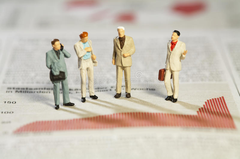 Business Strategy Meeting. Four miniature models of businessmen standing above a bar graph as though in a meeting royalty free stock photos