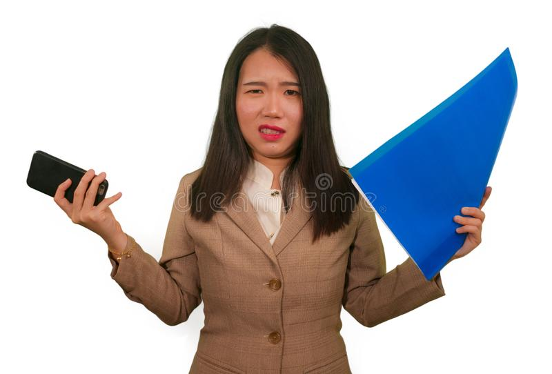Business stress portrait of young attractive upset and stressed executive Asian Chinese woman tired and unhappy holding paperwork royalty free stock photos