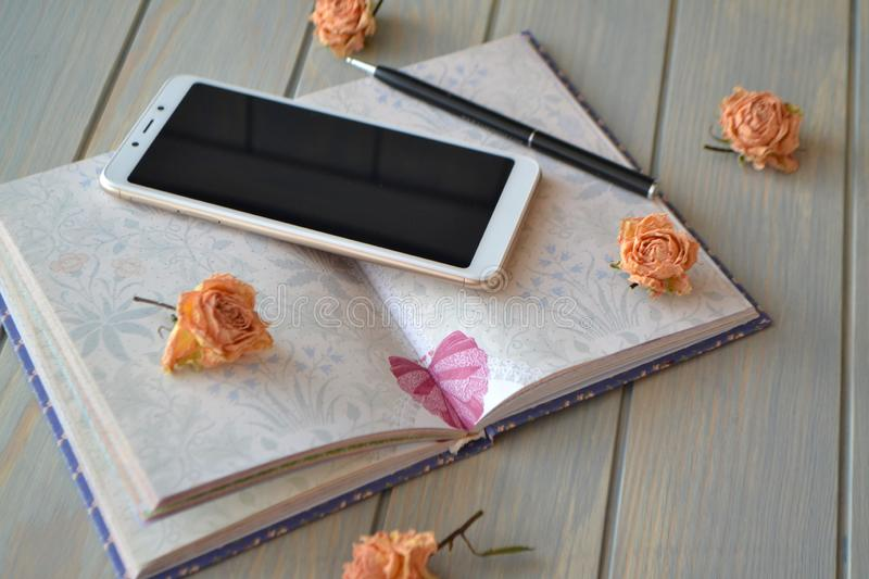 Business style, education or motivation image for women`s life style. Notebook, smartphone and vintage dry little roses stock images