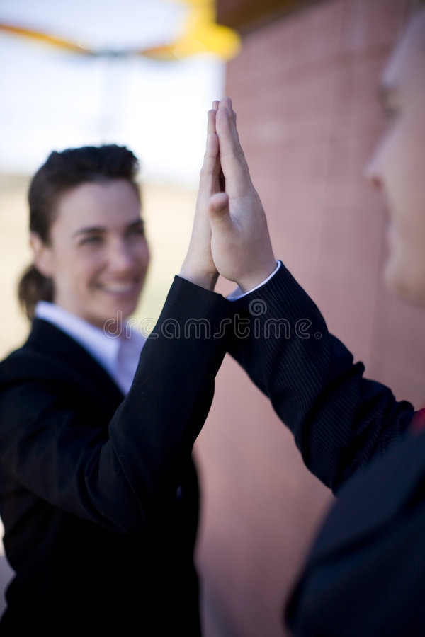 Business success. Businessman and businesswoman dressed in suits giving high-five stock image