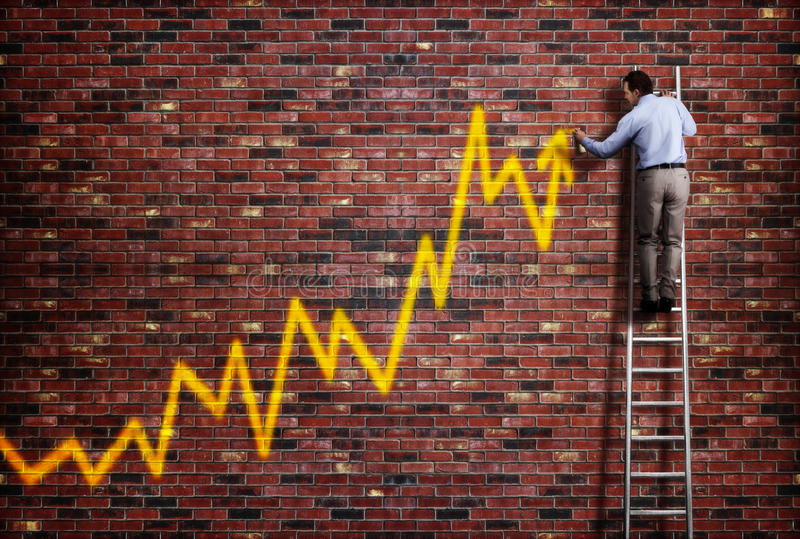 Business success. Businessman standing on a ladder and drawing a graph with positive trend in graffiti style yellow spray paint royalty free stock photography