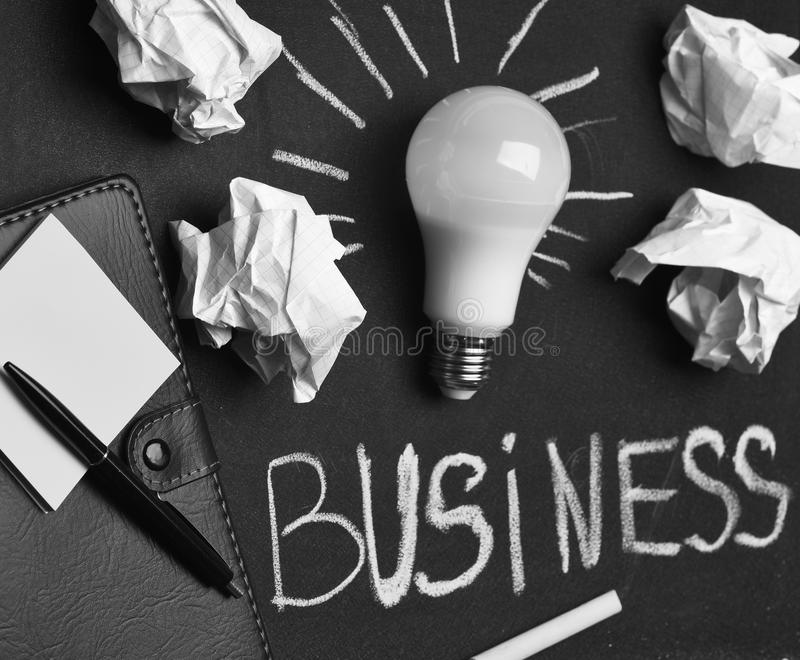 Business success concept. Board with light bulb, yellow chalk, pen and stickers. Process of creation: lamp, wrinkle paper, chalk and notebook. Chalkboard with royalty free stock photo