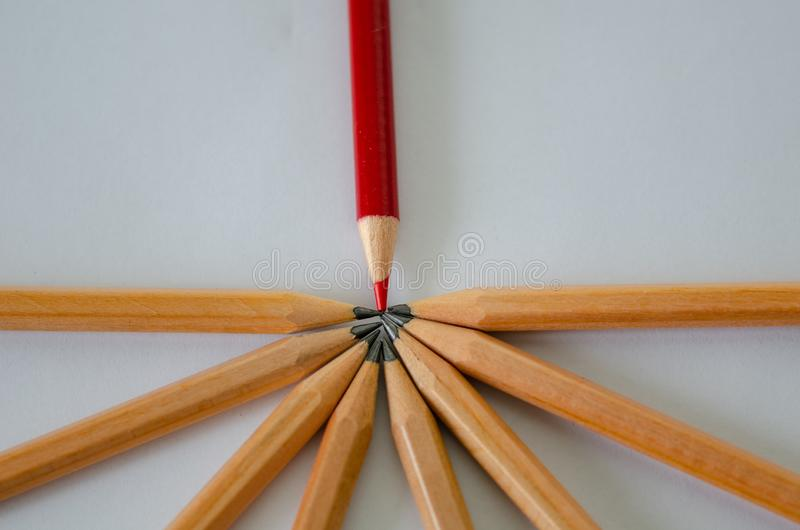 Business success concept,copy space. Red pencil standing out from crowd of plenty identical black pencil on white background. Leadership, uniqueness royalty free stock image
