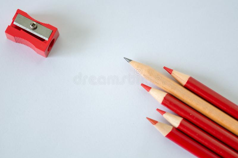 Business success concept,copy space. Yellow pencil standing out from crowd of plenty identical red pencil on white background. Leadership, uniqueness stock photo