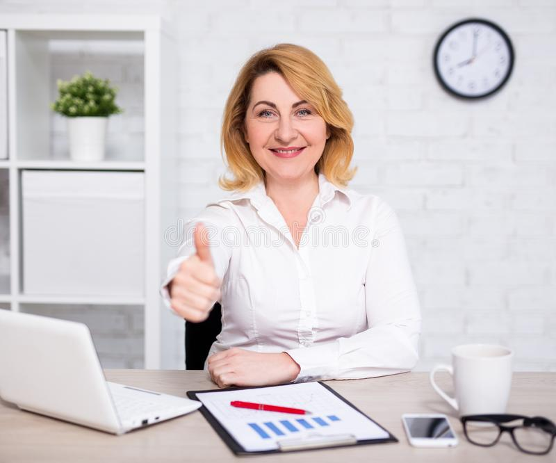 Business and success concept - happy mature business woman thumbs up in office stock image