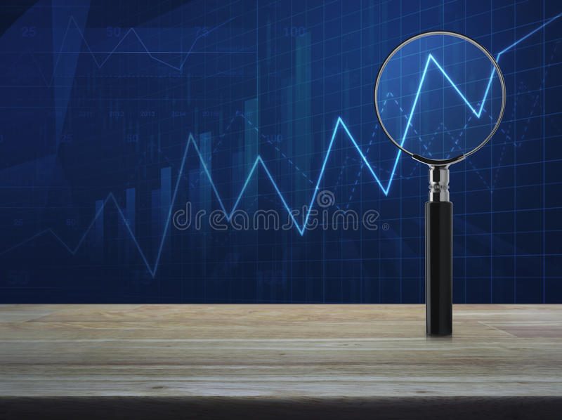 Business success concept. Magnifying glass with growth graph on wooden table over blue financial chart, Business success concept royalty free stock photography