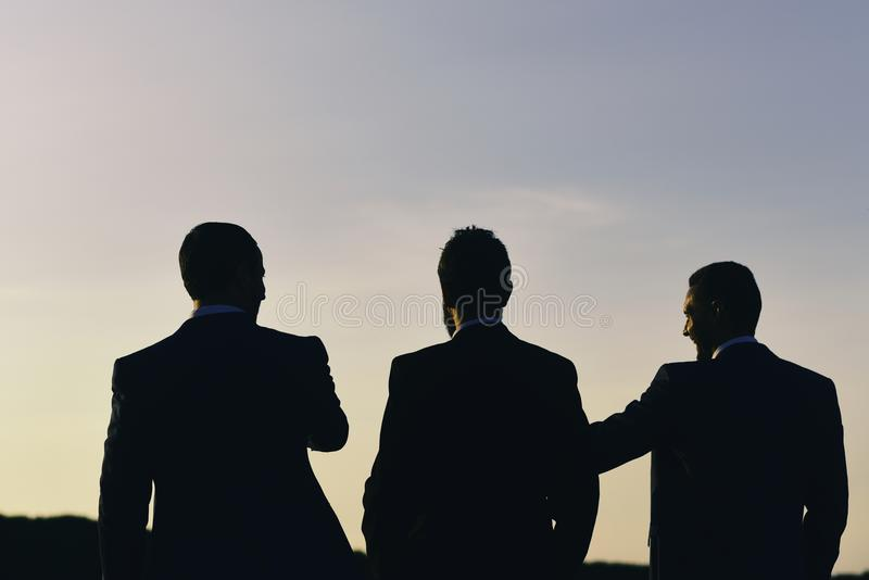 Business and success concept. Silhouettes of men standing against sunset. Leaders discuss project. royalty free stock images