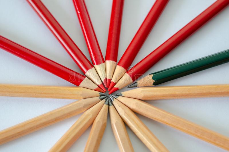 Business success concept. Two group of pencil and a green pencil. Leadership, uniqueness, independence, initiative, strategy, dissent, think different, business stock images