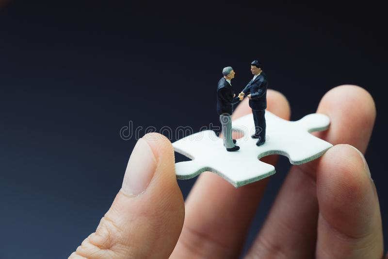 Business success strategy with collaboration, teamwork or negotiation jigsaw key, miniature people businessmen handshaking on stock photos