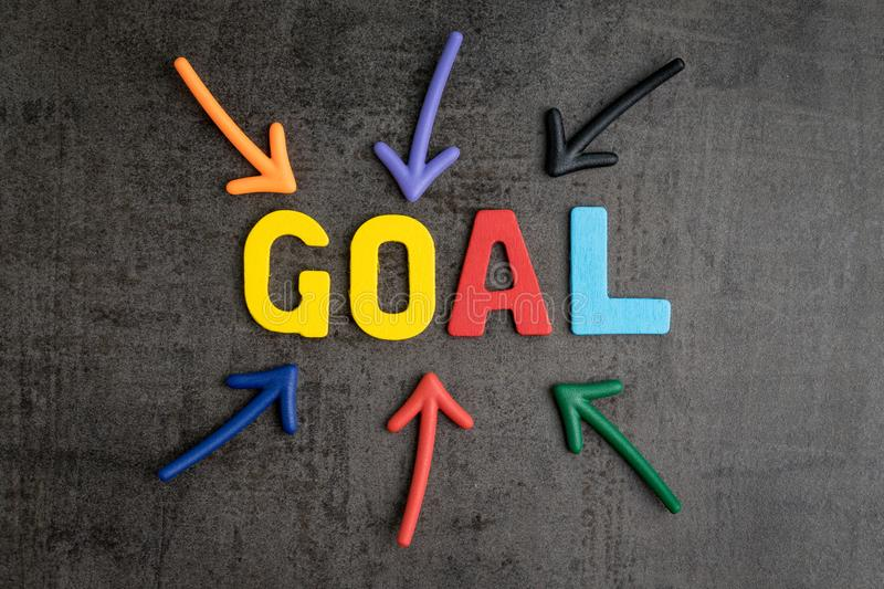 Business success strategy goals concept, colorful wooden alphabets GOAL at the center with pointing arrow on black chalkboard. Cement wall stock images