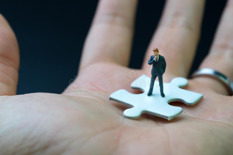 Business success strategy with missing jigsaw key person, miniature people businessman thinking and standing on white jigsaw. Puzzle piece in real human hand stock photos
