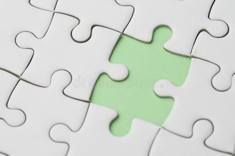 Business success strategy, problem, solution and answer metaphor. Concept, closed up of white jigsaw puzzle missing only one last piece to complete on pastel royalty free stock photos