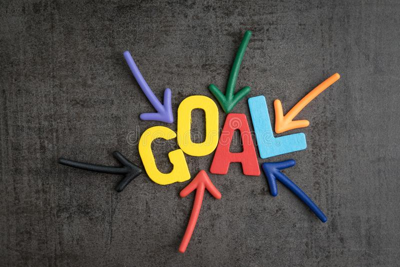 Business success target or goals concept, colorful wooden alphabets GOAL at the center with pointing arrow magnet on black. Chalkboard cement wall stock photos