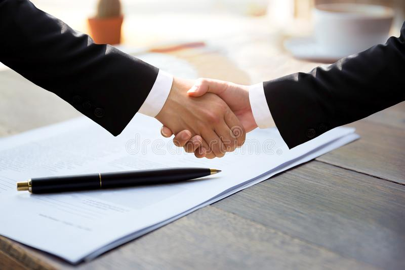 Business successful hand shaking hands over agreement form. Business successful hand shaking hands over pen and agreement form royalty free stock photography
