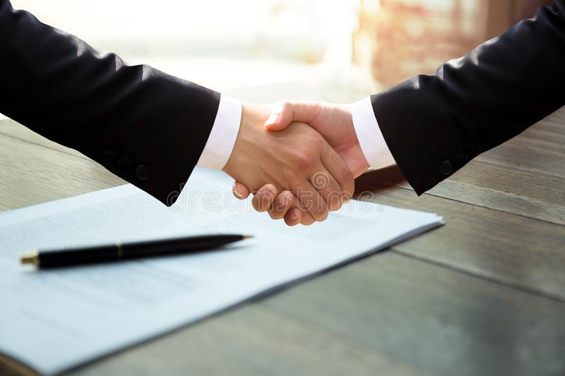 Business successful hand shaking hands over agreement form. Business successful hand shaking hands over pen and agreement form royalty free stock image