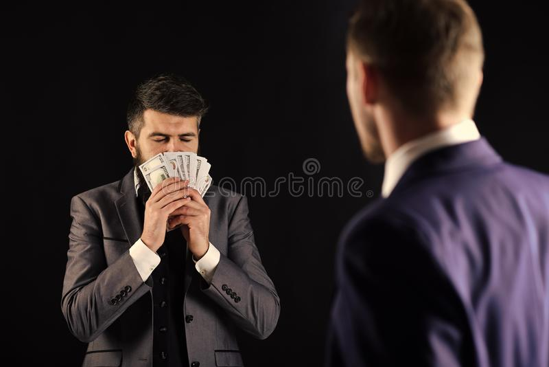 Business succsses. Man with beard on calm face sniffing money, smell of profit. Meeting of reputable businessmen, black royalty free stock image