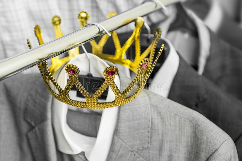 Business suit with a gold crown hanging on a hanger. Clothing is a successful person. Business concept. Metaphor.  stock image