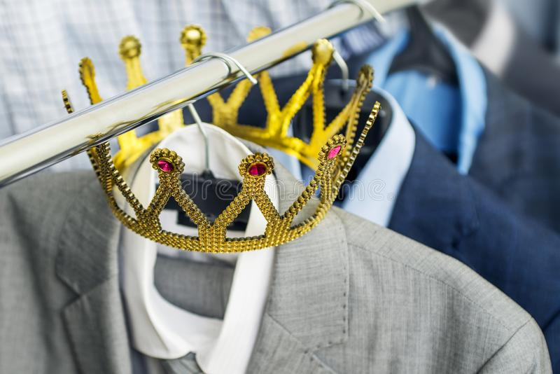 Business suit with a gold crown hanging on a hanger. Clothing is a successful person. Business concept. Metaphor.  royalty free stock photography