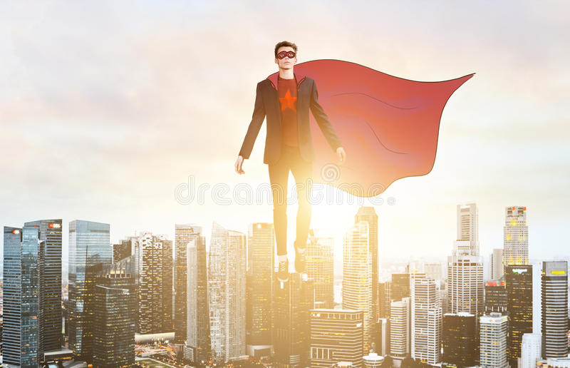 Business super hero hover over city skyline. Business superhero. Businessman hovering over down town on sunset stock image