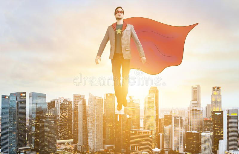 Business super hero hover over city skyline. Business superhero. Businessman in sketch super hero suit hovering over down town on sunset stock photography