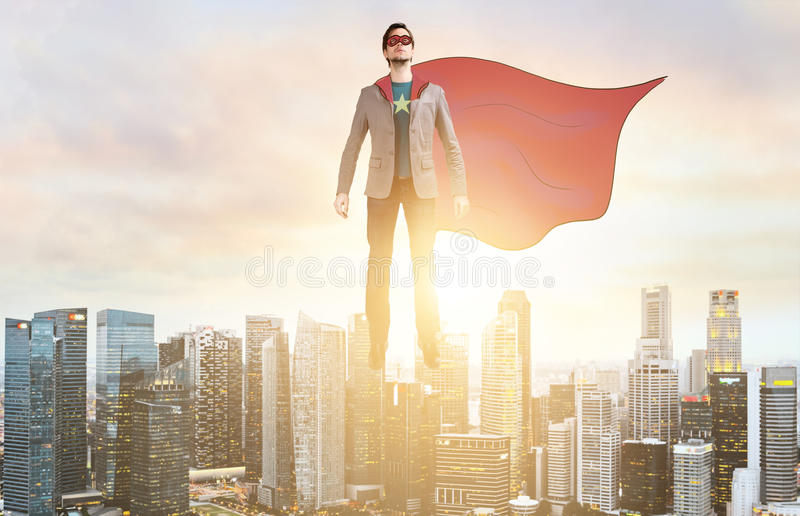 Business super hero hover over city skyline. Business superhero. Businessman in sketch super hero suit hovering over down town on sunset stock photos