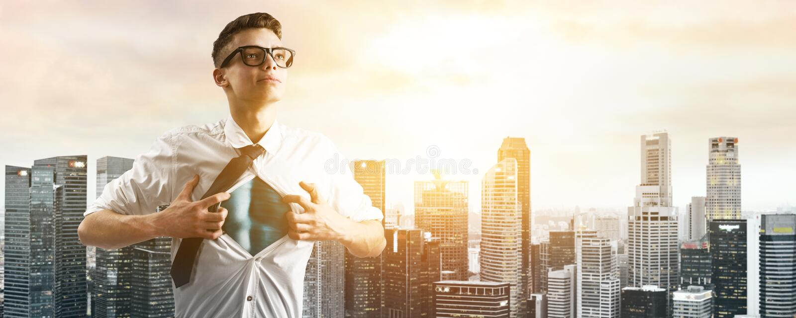Business super hero hover over city skyline. Business superhero. Young businessman showing super hero suit under his shirt down town on sunset royalty free stock photography