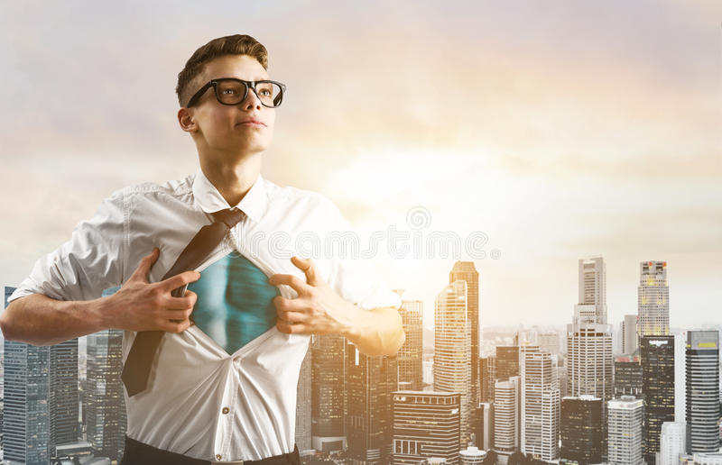Business super hero hover over city skyline. Business superhero. Young businessman showing super hero suit under his shirt down town on sunset royalty free stock image