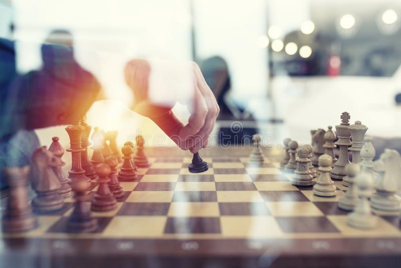 Business tactic with chess game and businessmen that work together in office. Concept of teamwork, partnership and royalty free stock photos