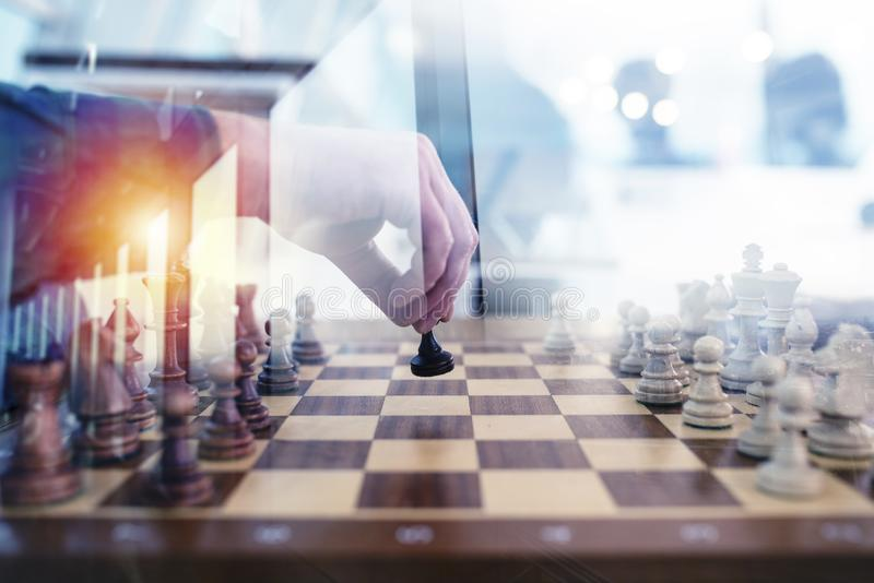 Business tactic with chess game and businessmen that work together in office. Concept of teamwork, partnership and stock photos