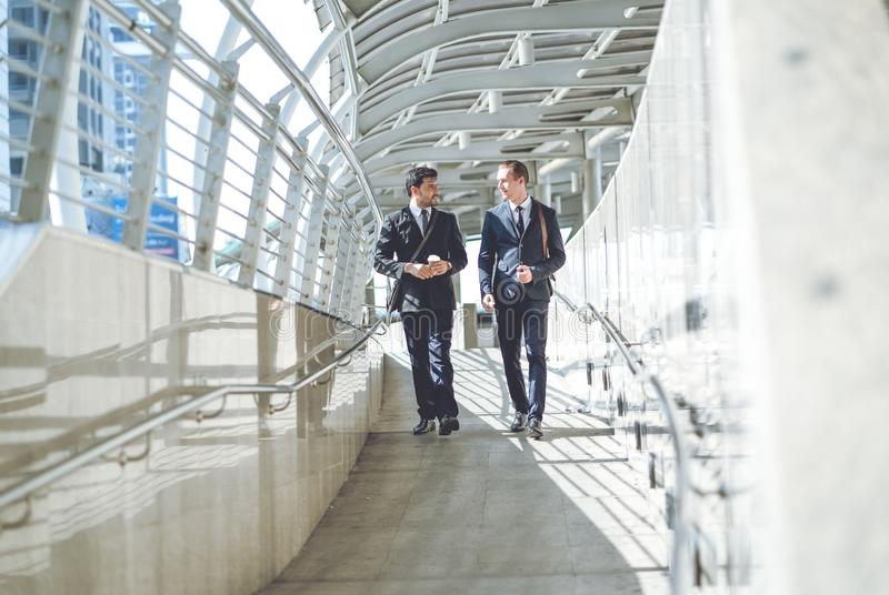 Business taliking.Two smiling young businessmen in elegant business suits, walking and talking in city street stock images