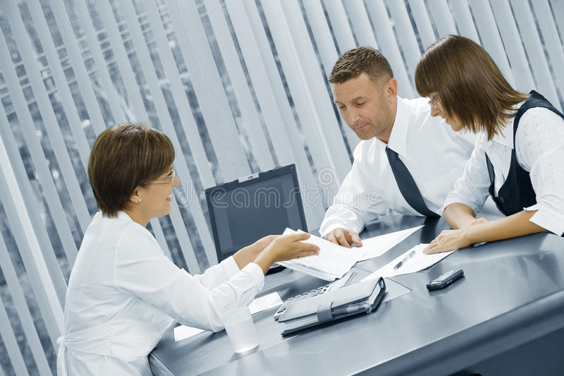 Business talk. Portrait of young business people discussing project in office environment stock image